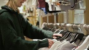 Una muchacha en un suéter verde y un sombrero amarillo camina a través de una tienda de cosas y elige qué comprar Cosas de los ta almacen de metraje de vídeo