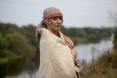 Una muchacha en un tocado viejo eslavo y capa de la era de Viking en la orilla del río fotografía de archivo