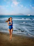 Una muchacha en un traje de baño está corriendo a lo largo de la playa imagen de archivo libre de regalías