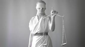 Una muchacha en un traje de piedra de la estatua Femida la diosa de la justicia en un fondo blanco en una mano que sostiene las e almacen de metraje de vídeo