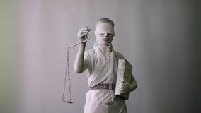 Una muchacha en un traje de piedra de la estatua Femida la diosa de la justicia en un fondo blanco en una mano que sostiene las e almacen de video