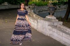 Una muchacha en un vestido abigarrado negro corre a través del puente Fotografía de archivo libre de regalías