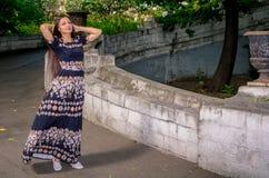 Una muchacha en un vestido abigarrado negro corre a través del puente Imágenes de archivo libres de regalías