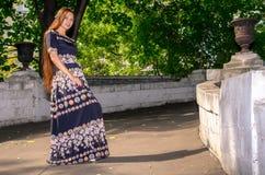 Una muchacha en un vestido abigarrado negro corre a través del puente Imagen de archivo