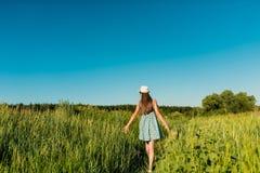 Una muchacha en un vestido azul con una hierba alta que camina el campo y que toca su mano de las espiguillas Fotos de archivo libres de regalías