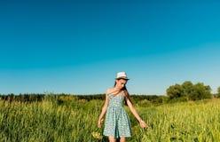 Una muchacha en un vestido azul con una hierba alta que camina el campo y que toca su mano de las espiguillas Foto de archivo