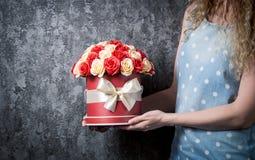 Una muchacha en un vestido azul está sosteniendo un ramo de rosas rojas y blancas en una caja del sombrero Fondo gris oscuro Imagenes de archivo