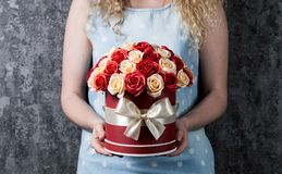 Una muchacha en un vestido azul está sosteniendo un ramo de rosas rojas y blancas en una caja del sombrero Fondo gris oscuro Fotos de archivo
