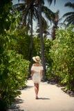 Una muchacha en un vestido blanco debajo de las palmeras maldives Vacaciones reconstrucción tropics Imágenes de archivo libres de regalías