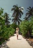 Una muchacha en un vestido blanco debajo de las palmeras maldives Vacaciones reconstrucción tropics Imagen de archivo