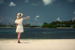 Una muchacha en un vestido blanco en la playa señala al océano maldives tropics reconstrucción Fotografía de archivo libre de regalías