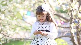 Una muchacha en un vestido blanco escucha la música a través de los pequeños auriculares audios