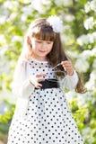 Una muchacha en un vestido blanco está sosteniendo un auricular audio Imágenes de archivo libres de regalías