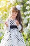 Una muchacha en un vestido blanco está sosteniendo un auricular audio Foto de archivo libre de regalías