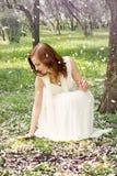 Una muchacha en un vestido blanco se agachó al lado del manzano floreciente en el jardín Los pétalos vuelan del árbol, magia y Foto de archivo libre de regalías