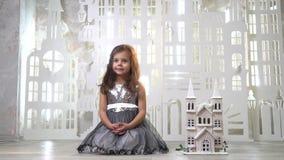 Una muchacha en un vestido con las lentejuelas se sienta en un cuarto al lado de una cerradura del juguete, en el fondo un pájaro almacen de video
