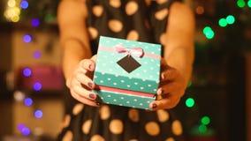 Una muchacha en un vestido de noche da un regalo del Año Nuevo almacen de metraje de vídeo