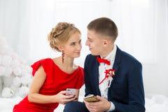 Una muchacha en un vestido rojo con un individuo que sostiene un teléfono móvil Fotos de archivo