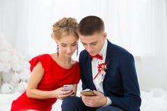 Una muchacha en un vestido rojo con un individuo que sostiene un teléfono móvil Foto de archivo