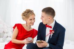 Una muchacha en un vestido rojo con un individuo que sostiene un teléfono móvil Fotos de archivo libres de regalías