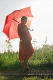Una muchacha en un vestido rojo se está colocando en el camino con un paraguas rojo grande Imagenes de archivo