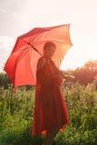 Una muchacha en un vestido rojo se está colocando en un campo con un paraguas rojo grande Foto de archivo