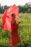 Una muchacha en un vestido rojo se está colocando en un campo con un paraguas rojo grande Foto de archivo libre de regalías