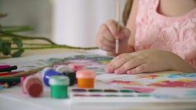 Una muchacha en un vestido rosado dibuja las flores con un cepillo, cámara lenta almacen de video