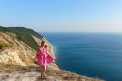 Una muchacha en un vestido rosado salta en la costa Imágenes de archivo libres de regalías
