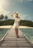 Una muchacha en un vestido y un sombrero blancos se está colocando en un puente maldives Isla tropics Fotos de archivo