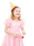 Una muchacha en una alineada rosada y una risa festiva del sombrero Imagenes de archivo