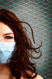 Una muchacha en una máscara protectora imagenes de archivo