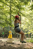 Una muchacha en una polea en un parque de la cuerda Imagen de archivo libre de regalías