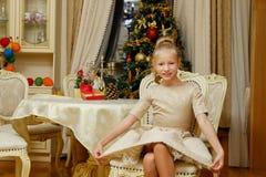 Una muchacha en vestido de noche en un cuarto con la decoración de la Navidad Foto de archivo libre de regalías