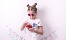 Una muchacha en vidrios rosados utiliza un smartphone rojo Fotos de archivo libres de regalías