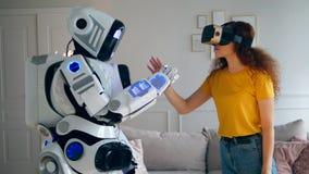 Una muchacha en VR-vidrios está entrando en contacto con con un robot almacen de metraje de vídeo
