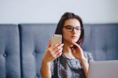 Una muchacha encantadora en vidrios para un ordenador portátil que hace un selfie Imagenes de archivo