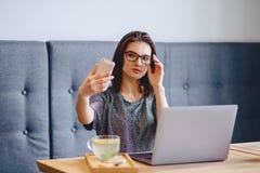 Una muchacha encantadora en vidrios para un ordenador portátil que hace un selfie Imágenes de archivo libres de regalías