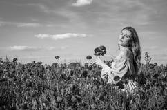 Una muchacha encantadora joven con el pelo largo camina en un día de verano soleado brillante en un campo de la amapola y hace un Imagenes de archivo