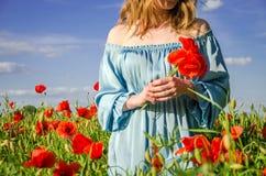 Una muchacha encantadora joven con el pelo largo camina en un día de verano soleado brillante en un campo de la amapola y hace un Foto de archivo libre de regalías