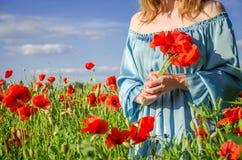 Una muchacha encantadora joven con el pelo largo camina en un día de verano soleado brillante en un campo de la amapola y hace un Imagen de archivo