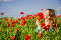 Una muchacha encantadora joven con el pelo largo camina en un día de verano soleado brillante en un campo de la amapola y hace un Fotos de archivo libres de regalías
