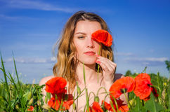 Una muchacha encantadora joven en un campo de la amapola cierra un ojo con una flor de la amapola en un día de verano soleado bri Foto de archivo