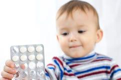 Una muchacha enferma con las píldoras en sus manos Imagenes de archivo