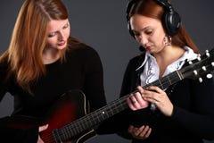 Una muchacha enseña a otra para tocar la guitarra Imagen de archivo libre de regalías