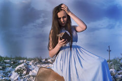 Una muchacha entre una descarga de basura se sienta en una maleta con una cartera vacía en un fondo del cielo azul Imagen de archivo libre de regalías