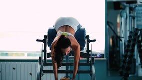 Una muchacha entrena a los músculos de la parte posterior en gimnasio almacen de metraje de vídeo
