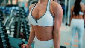 Una muchacha entrena a los músculos de los brazos con pesas de gimnasia metrajes
