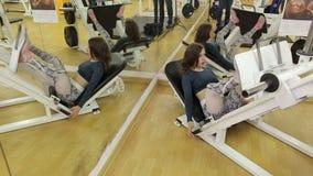 Una muchacha entrena a los músculos de sus piernas en gimnasio, ella hace la prensa de la pierna que se acuesta metrajes