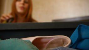 Una muchacha es maleta abierta y los vidrios el poner en la maleta defocuse Dentro de vista de una maleta Trevels felices metrajes